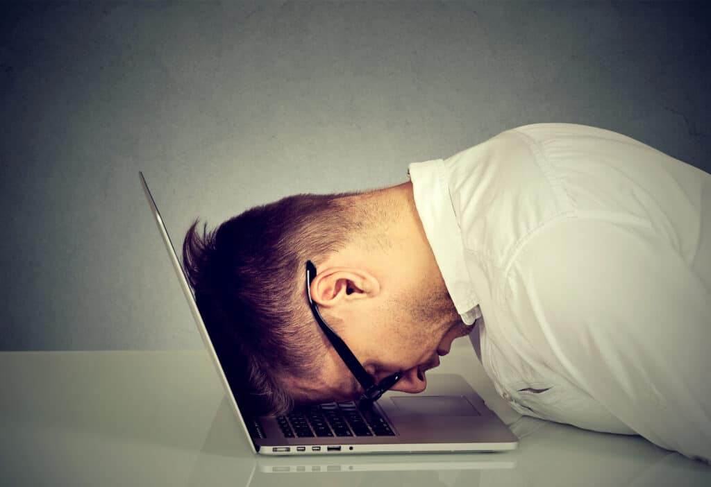 Desperate employee, stressed young man resting head on laptop keyboard