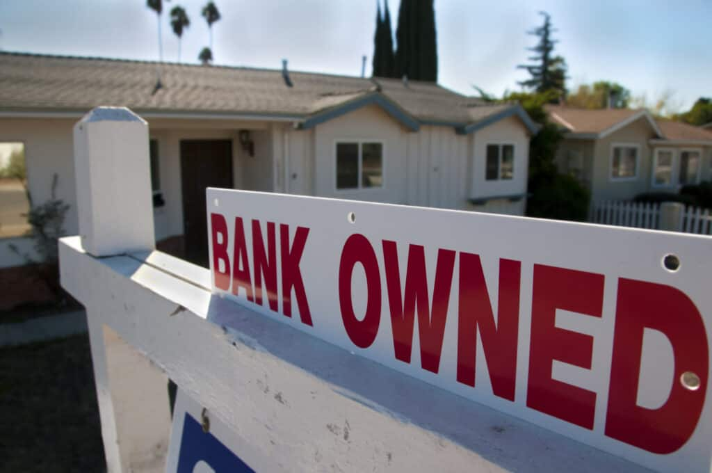 A foreclosed home shows a bank owned for sale sign