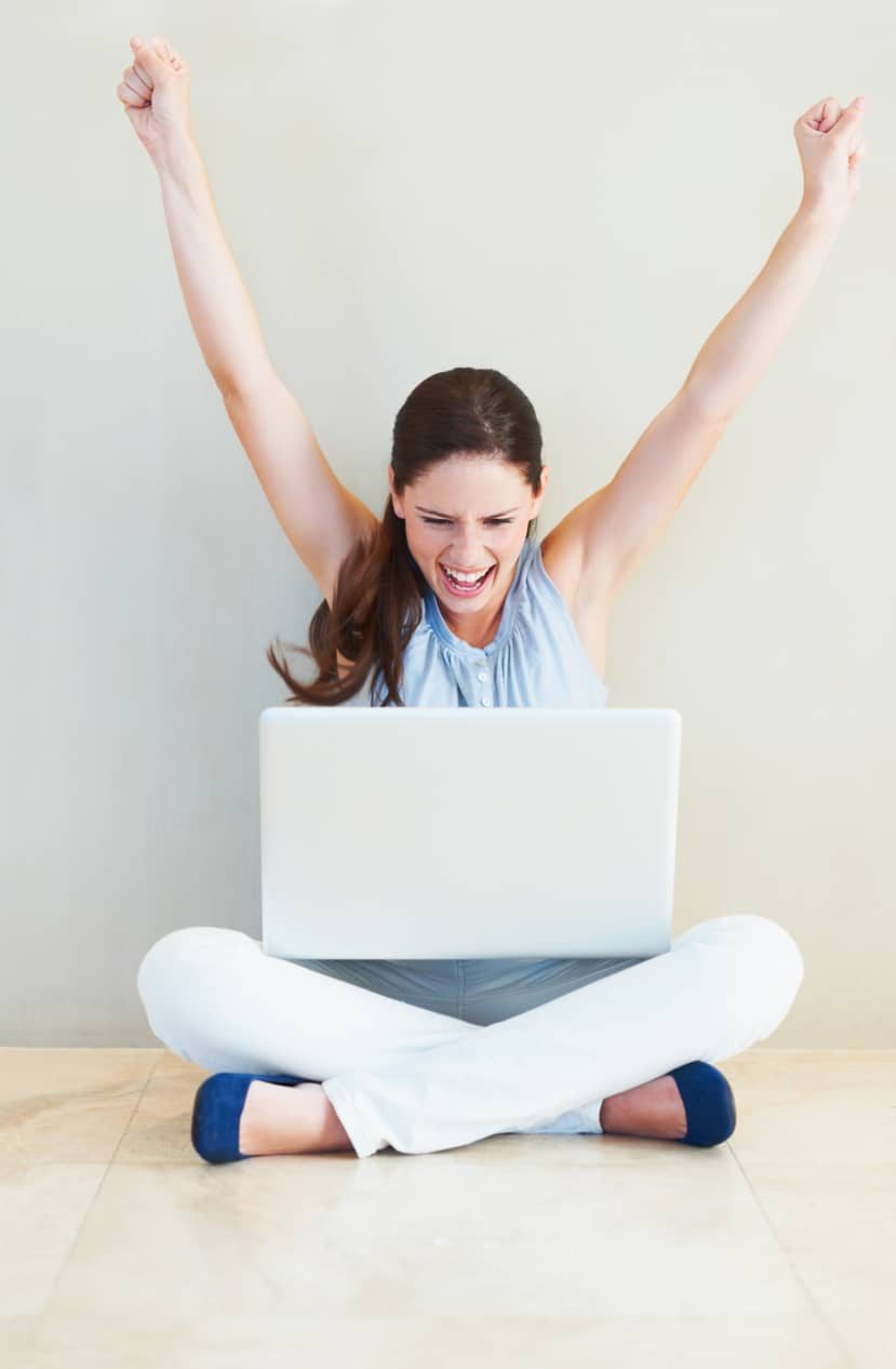 A pretty young woman cheering while looking at her laptop screen