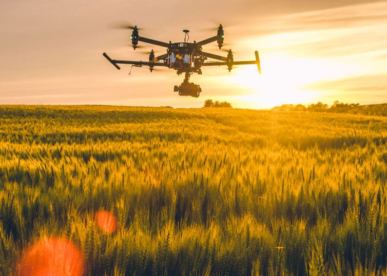 Drone technology in action: An aerial drone flying over a field at sunset