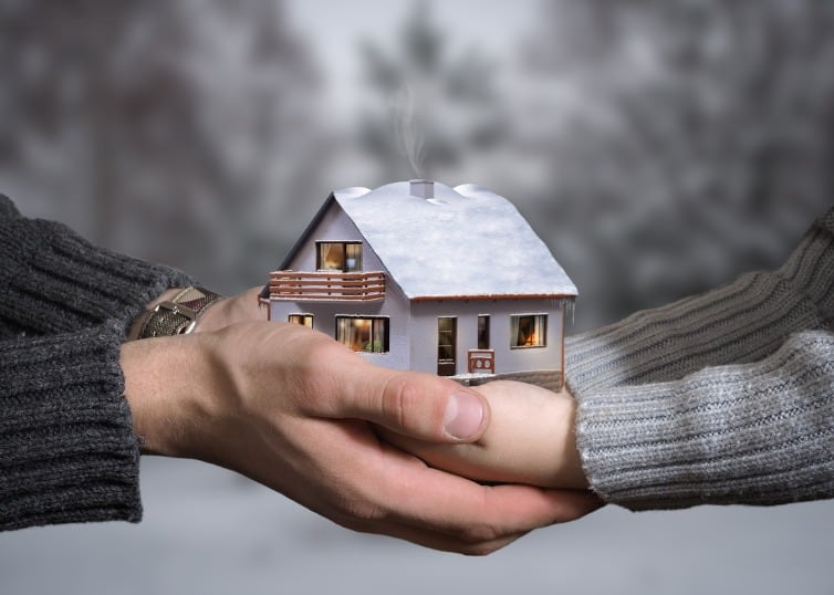 the hands of an adult and child hold a winter house