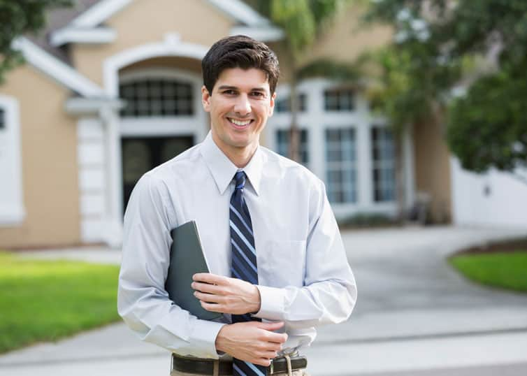Real estate appraiser who specializes in appraising luxury homes standing outside a high-end home