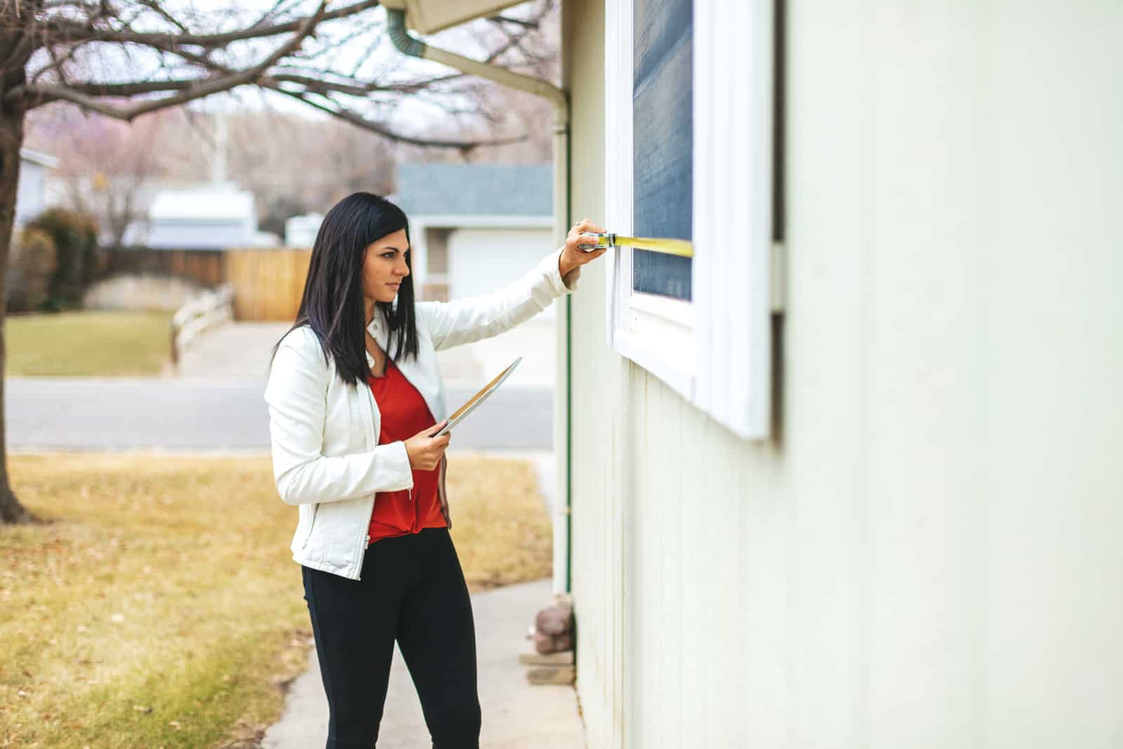 Young Adult Millennial Female Appraiser Measuring Home Features and Assessing Value in Western Colorado