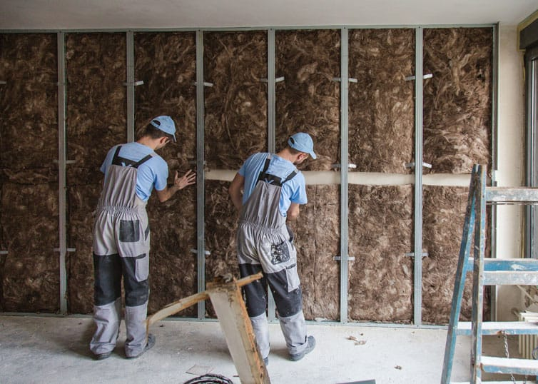 Construction site close up with workers installing glass wool sustainable insulation
