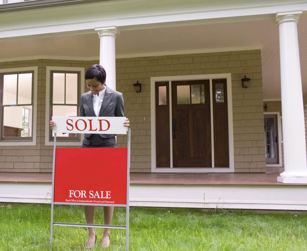 real estate agent with sign in front yard