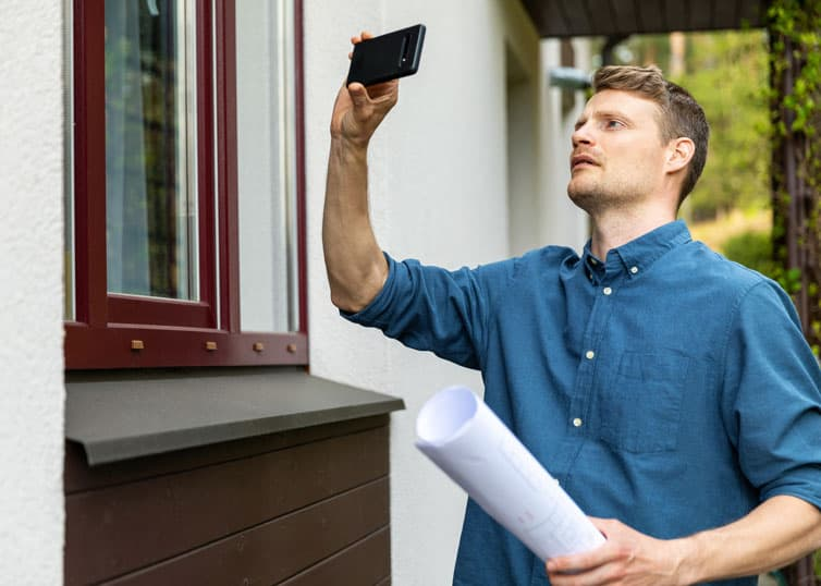 Real estate appraiser completing taking photos on phone