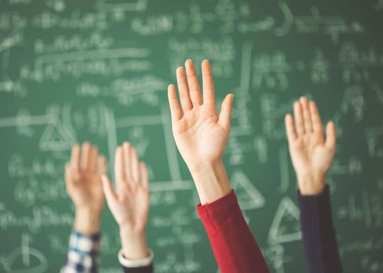 Students' hands raised in front of green chalkboard coverd in math problems