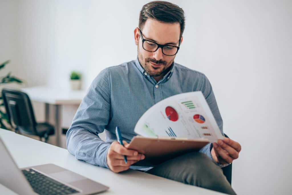 Businessman reading document at desk in office