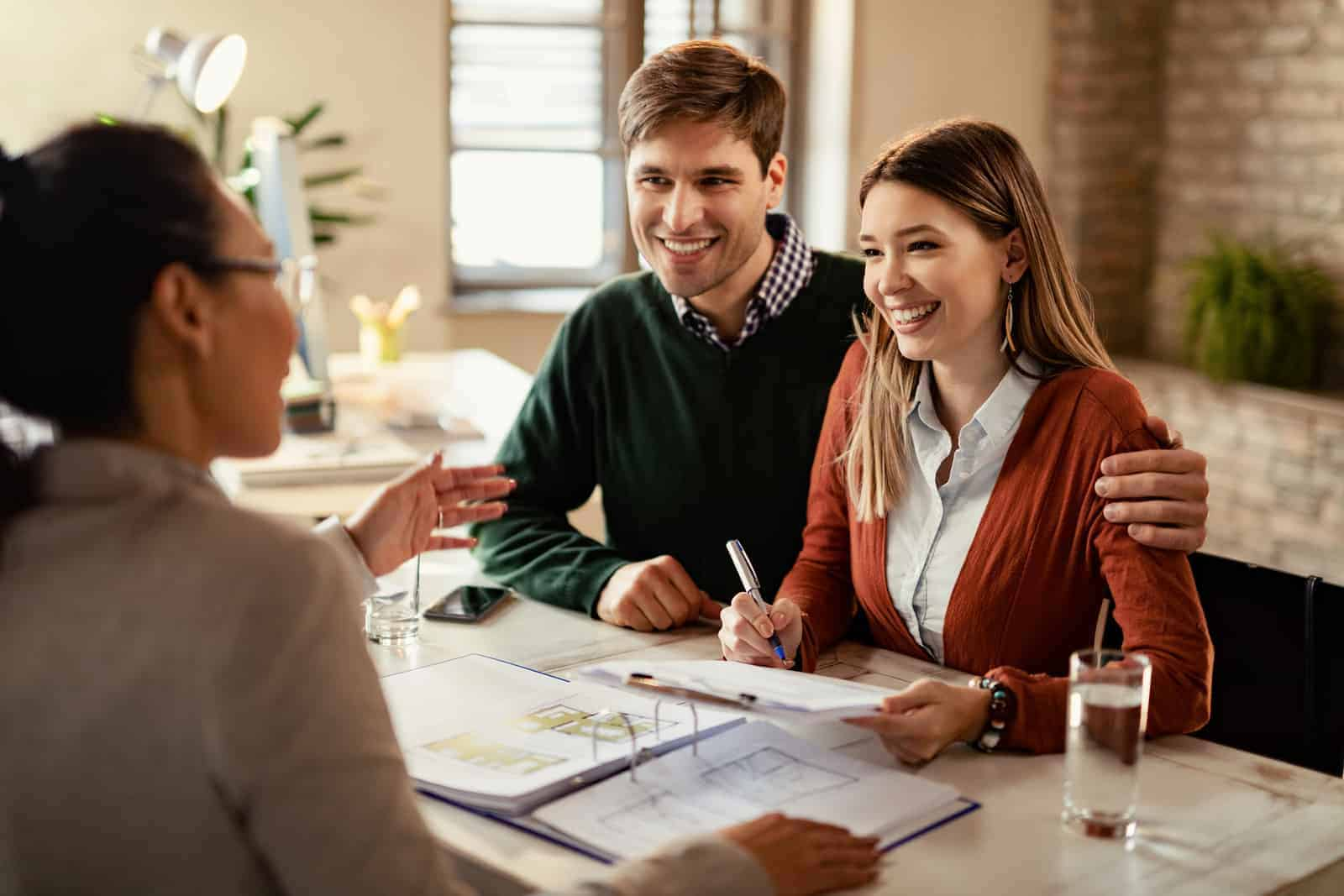Happy couple signing mortgage contract while having meeting with real estate agent.
