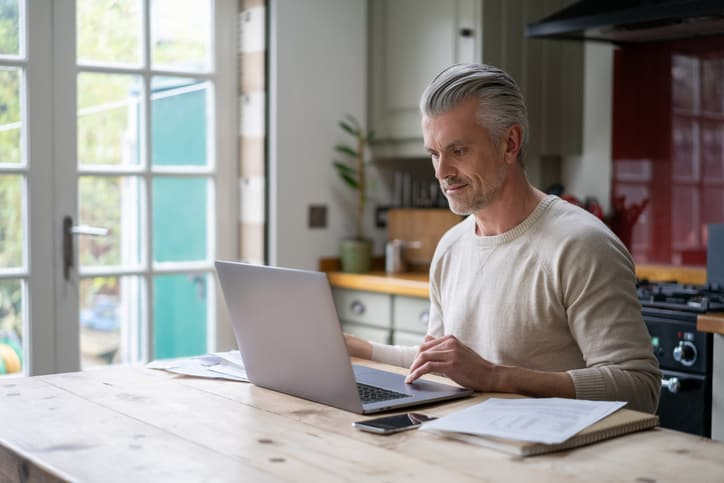 Man working at home on laptop, researching how to specialize in appraising green homes