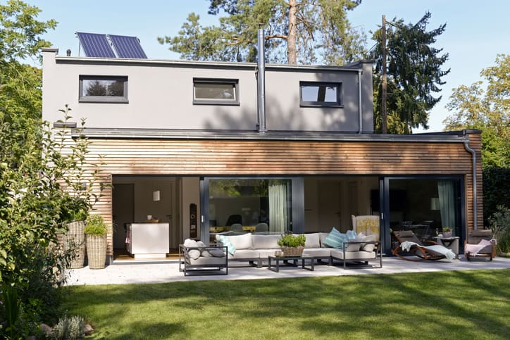 Modern detached house with green home features, rooftop solar panels, terrace and garden