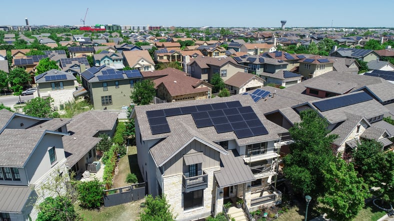 Aerial drone view of homes with solar panel rooftops in East Austin suburban neighborhood